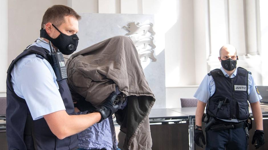 Der Angeklagte wird während des Prozessauftakts um die Gewalttat in Rot am See vor dem Landgericht Ellwangen in den Gerichtssaal geführt.