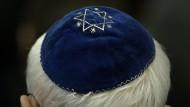 Ein Mann trägt in der Synagoge in Mainz eine Kippa.