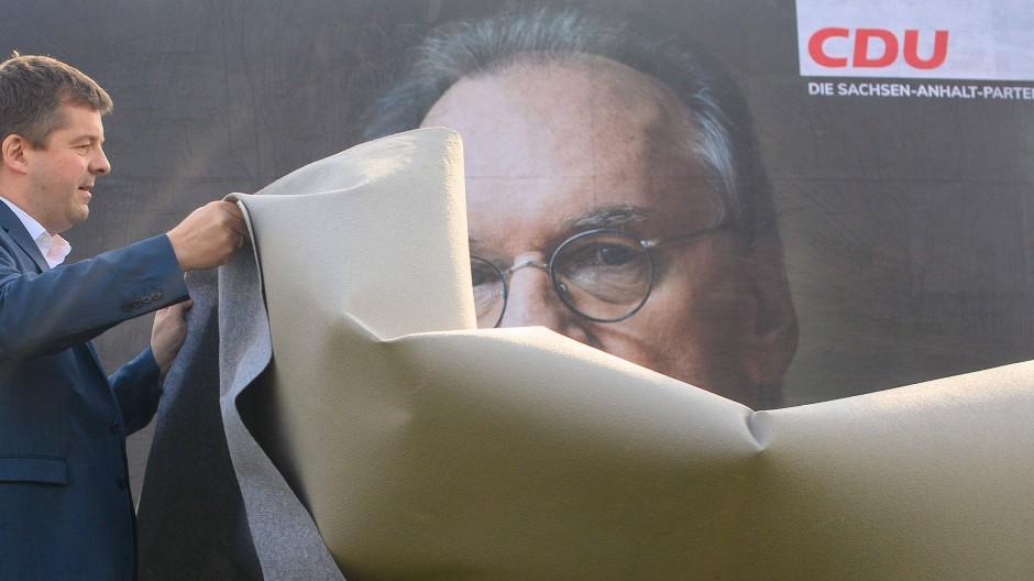 Sven Schulze, Vorsitzender der CDU Sachsen-Anhalt, enthüllt ein Wahlplakat der CDU, auf dem ein Porträt des Ministerpräsidenten Reiner Haseloff zu sehen ist.