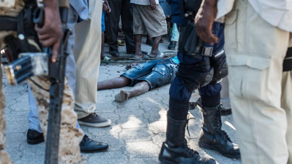 Polizisten stehen um den Leichnam eines Häftlings, der bei dem Massenausbruch aus einem Gefängnis in Haiti ums Leben kam.