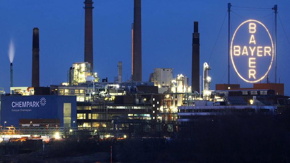 Das Bayer-Logo leuchtet über dem Werksgelände in Leverkusen.