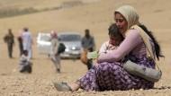 Eine jesidische Frau mit ihrem Kind auf der Flucht vor der Gewalt der IS-Kämpfer. Die Jesiden leben vor allem im Nordirak.