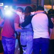 Eine verletzte Konzertbesucherin wird von Helfern in Sicherheit gebracht.