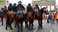 Am Brandenburger Tor versuchen Polizeibeamte beide Gruppen voneinander fernzuhalten.