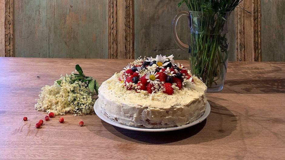 Schmeckt nicht nur gut, sieht verziert mit Beeren und Blumen auch gut aus: eine Torte mit Holunderblüten-Mascarpone und frischen Erdbeeren.