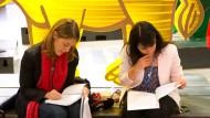 Was steht drin? Am Rande der Klimakonferenz in Paris arbeiten zwei Beobachterinnen den Vertragsentwurf durch.