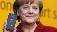 Merkel präsentiert stolz ein Smartphone