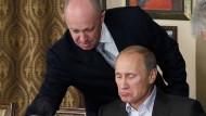 """Der Chef und sein Handlanger: Jewgenij Prigoschin, dem die """"Wagner""""-Gruppe zugeordnet wird, bedient Wladimir Putin 2011 in seinem Restaurant in der Nähe von Moskau."""