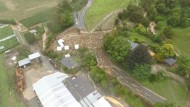 Eine Drohnenaufnahme zeigt, wie Erdmassen eine Straße auf dem Takaka Hill im Norden der Südinsel blockieren.