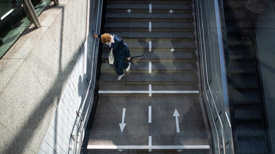 Mit Abstand und festgelegten Verkehrsrichtungen durch den Corona-Alltag: Eine ältere Frau steigt in Hamburg die Treppen einer U-Bahn-Station hinab. Das Leben in der Pandemie stellt für viele Menschen auch psychologisch eine Herausforderung dar.