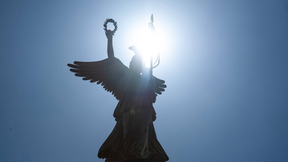 Die Sonne scheint durch die Statue der Viktoria auf der Berliner Siegessäule.