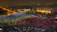 Mit Handylichtern, die durch farbiges Papier scheinen, bilden Demonstranten die rumänische Flagge.