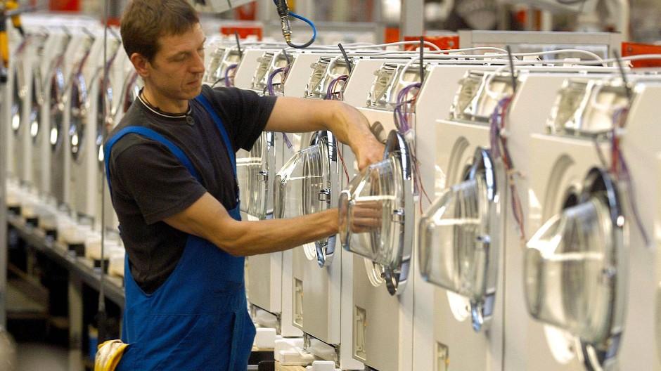 An einer Produktionsstraße für Waschautomaten arbeitet ein Miele-Mitarbeiter in Gütersloh.