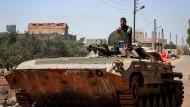 Soldaten der syrischen Regierungstruppen patroullieren nach der Rückeroberung von Kiheel auf einem Panzerfahrzeug durch den Ort.