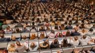 Studenten verfolgen im Hörsaal im Hauptgebäude der Universität zu Köln in Köln (Nordrhein-Westfalen) die Erstsemesterbegrüßung.