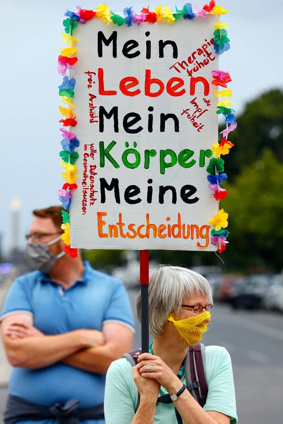 """Eine Demonstrantin mit einem Netz vor dem Mund hält ein Schild hoch: """"Mein Leben, mein Körper, meine Entscheidung"""""""