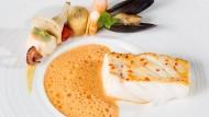 Puristisch gegarter Fisch mit im Halbmond drapierten Beilagen aus Meeresfrüchten.