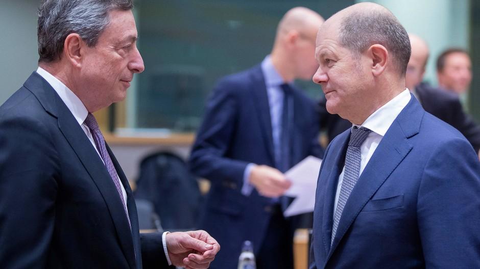 Mario Draghi (l.), Präsident der Europäischen Zentralbank, spricht mit Bundesfinanzminister Olaf Scholz während eines Treffens der EU-Finanzminister.