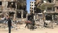 Menschen stehen vor zerstörten Gebäuden in Douma, der syrischen Stadt, in der es angeblich zu einem Giftgasangriff gekommen sein soll