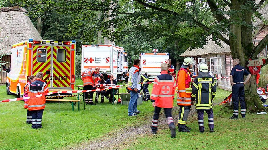 Feuerwehrmänner, Rettungskräfte und Rettungsfahrzeuge stehen während des Notfalleinsatzes in Handeloh vor dem Tagungszentrum.