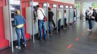 Bankkunden am Geldautomaten.