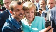 Die Kanzlerin hat sich verändert – und wie ändert sich das Land? Angela Merkel macht ein Selfie mit Flüchtling in Berlin-Spandau.