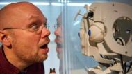 """Menschliches Vorbild: Roboter """"Felix"""" ahmt Grimassen nach, die Philipp Horst ihm schneidet. Horst ist Projektleiter der Ausstellung """"Die Roboter"""" in Dortmund."""