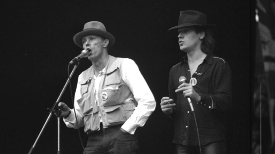 Auf der Bühne am Tag der Bonner Friedensdemonstration: Hinweise darüber, was diese zwei Hutträger da zusammen sangen, nimmt die Redaktion gern entgegen.