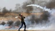 Ein palästinensischer Demonstrant versucht bei Protesten an der Grenze zu Israel im Gazastreifen mit einem Schläger eine Tränengaskartusche abzuwehren.
