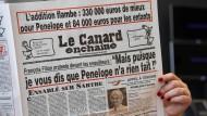 Eine Journalistin liest eine der Ausgaben über den Skandal um François Fillon.