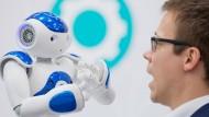 """Angeregte Diskussion: Roboter """"Nao"""" und Systemadministrator Philipp Bültmann unterhalten sich bei der Cebit in Hannover."""