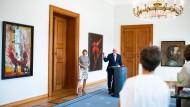 """Frank-Walter Steinmeier und seine Frau Elke Büdenbender vor dem """"Seiltänzer"""" von Trak Wendisch, rechts dahinter Harald Mentzkes """"Januskopf"""". Links hängt inks """"Kaspar – kopfüber in Damenstiefeln"""" (1987) von Hartwig Ebersbach."""