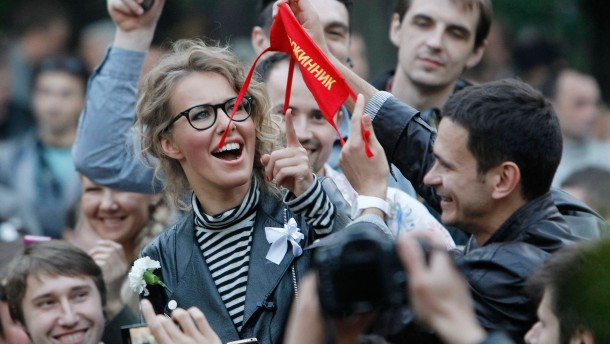 Opposition leader Yashin shows a security patch as television host and opposition activist Sobchak looks at it as opposition try to set on their own security at protest camp in a boulevard in central Moscow