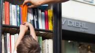Früh reckt sich, was ein Leser werden will: junger Interessent vor offenem Bücherschrank in Frankfurt