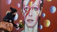 Vor einem Wandgemälde in David Bowies Londoner Heimatviertel Brixton legen Fans zu Ehren des Sängers Blumen nieder.