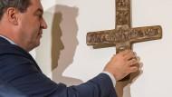 Markus Söder hängt ein geweihtes Kreuz in der Staatskanzlei auf.