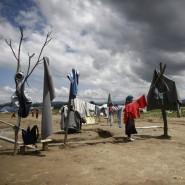 Nach heftigen Regenfällen hängt eine Frau im Flüchtlingslager bei Idomeni Sachen zum Trocknen auf.