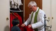 Mit einem Schutzkonzept gegen sexuellen Missbrauch in der Kirche: Der Wuppertaler Pfarrer Bruno Kurth hilft einem Messdiener beim Anlegen des liturgisches Gewandes.