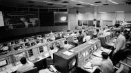 Mächtige Rechner, doch Papier und zuschaltbare Experten im Hintergrund waren nicht minder wichtig: das Mission Control Center in Houston 1968 beim Flug von Apollo 8, an dem David Gugerli die Synchronisierung von Computer und Welt vorführt, deren Emblem das von den Astronauten aufgenommene und rechts eingespielte Bild der Erde ist.