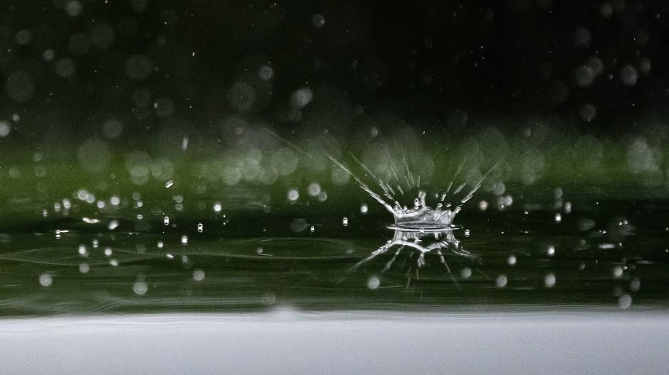 Aus der Nähe ein Spektakel: Regentropfen fallen auf ein Autodach.