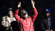 Kontrast zum zeremoniösen Ambiente: Kanye West erscheint zur Modenschau im Schlabberlook.