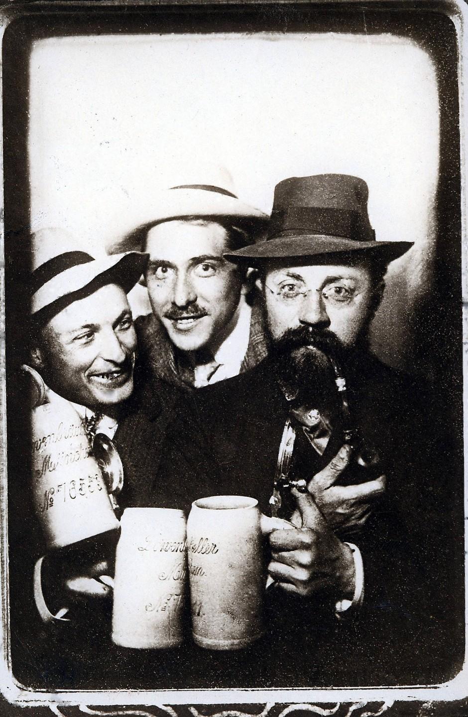 Ein Prosit der Gemütlichkeit: Henri Matisse mit Pfeife und seinen deutschen Künstlerfreunden Hans Purrmann und Albert Weisgerber im Münchner Löwenbräukeller am Sofortbildautomaten 1910