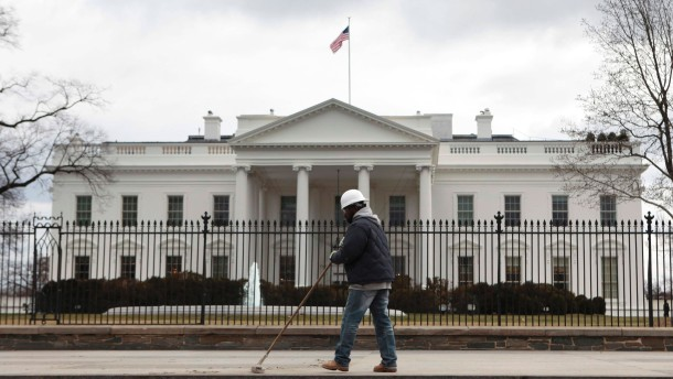 A worker cleans a sidewalk outside the White House