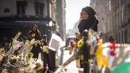 Eine Trauernde steht vor der Pizzeria Casa Nostra in Paris.