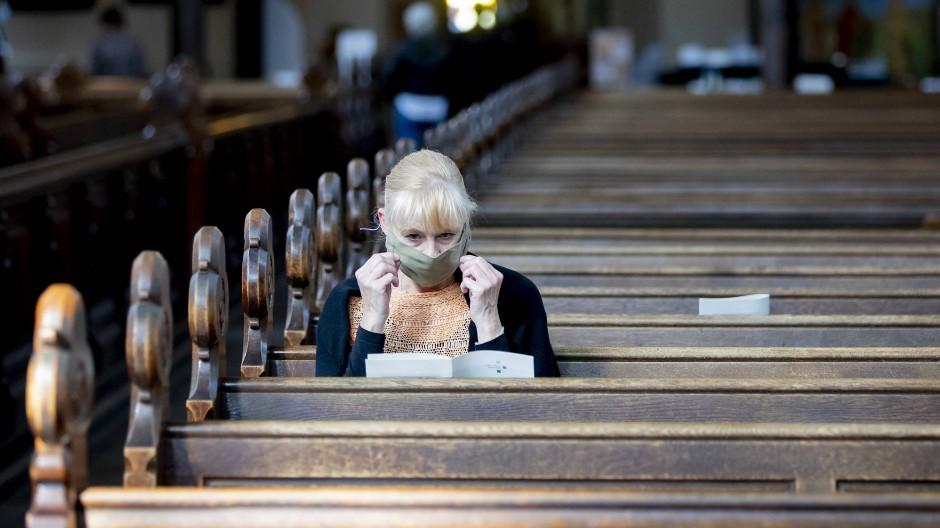 Besucherin mit Mundschutz in der St. Marienkirche in Berlin. Maximal fünfzig Gläubige dürfen hier derzeit einen Gottesdienst besuchen.