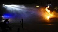 Ein Wasserwerfer als Feuerwehr: Polizisten löschen am 8. Juli eine brennende Barrikade in Hamburg.