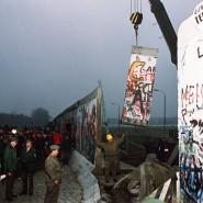 Teile der Berliner Mauer werden am 11. November 1989 mit Hilfe eines Krans entfernt. Zahlreiche Menschen verfolgen in der Nacht die Aktion.
