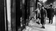 Die Fassungslosigkeit im Blick: Am Tag nach der Pogromnacht macht sich ein junger Mann in Frankfurt daran, die Schaufensterscherben zusammenzukehren.
