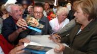 Es kann nicht immer nur um ihre eigenen Bücher gehen: Angela Merkel signiert im Juli 2005 in einer Bücherei in Westerland auf Sylt ihr Buch Mein Weg.