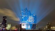 Der gläserne Neubau mit seiner kühn geschwungenen Dachlandschaft erhebt sich auf dem Sockel eines ehemaligen Kaispeichers an der westlichen Spitze der Hafencity.